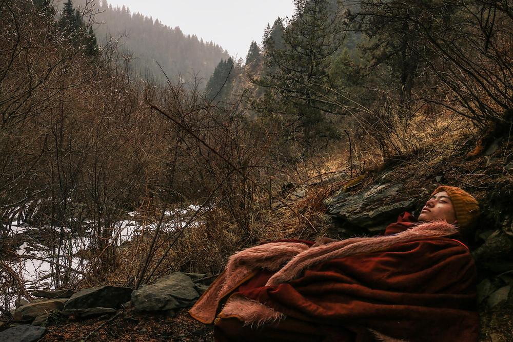 Joven monje tibetano reposando en el bosque