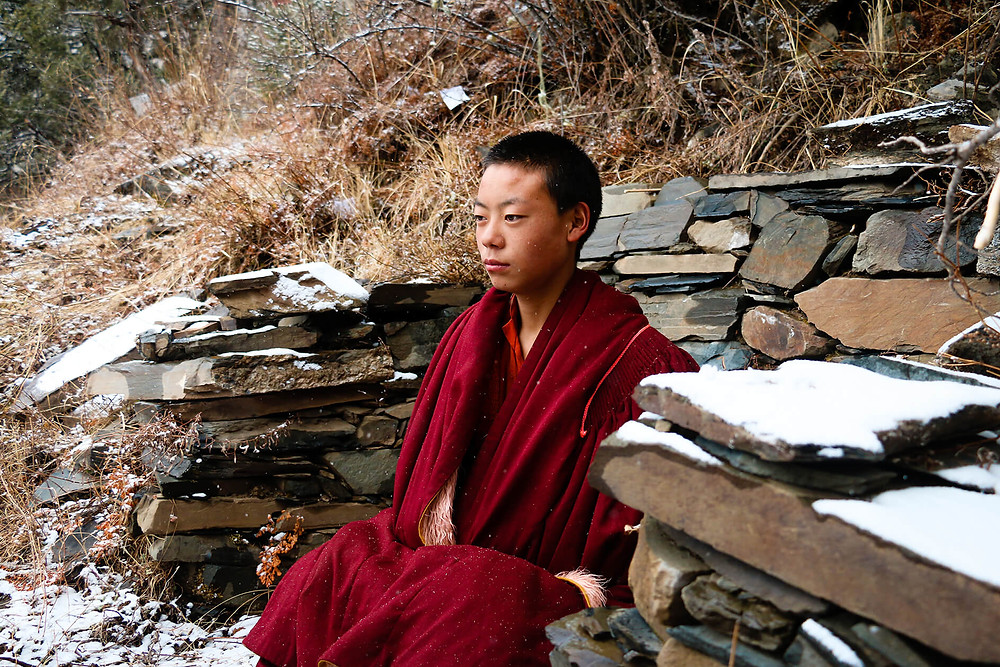 Tibetan young monk meditating in the mountains