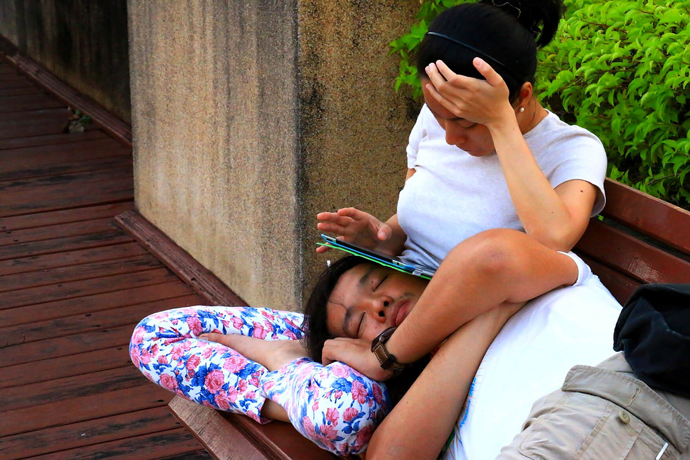 Woman using a tablet over the head of her boyfriend at a park in Thailand