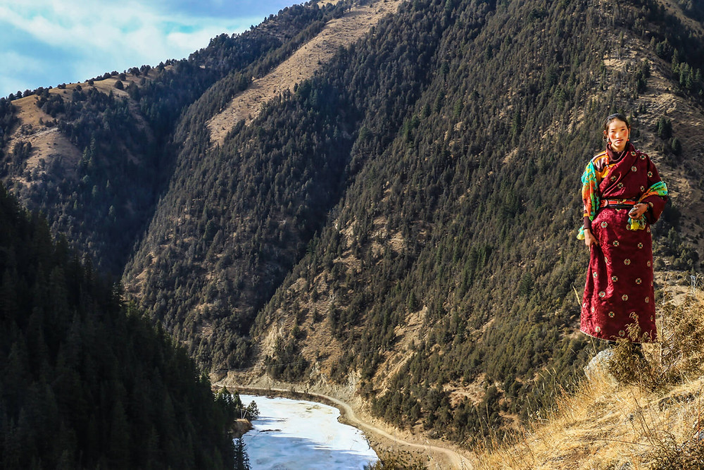 Mujer tibetana de pie, en un paisaje de montañas junto a un río