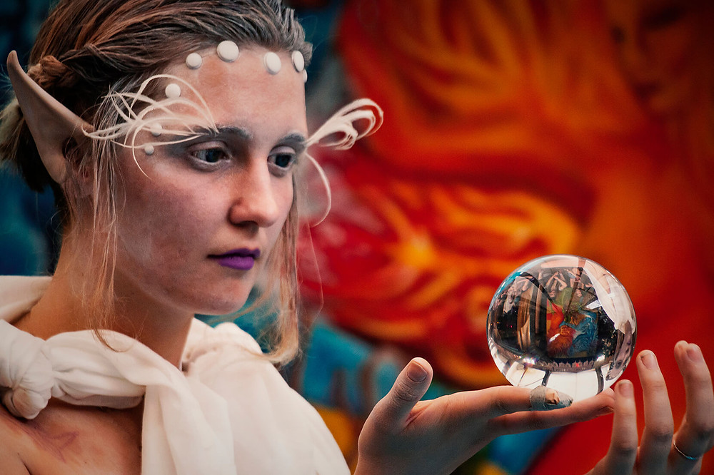 An Elf girl in front of a glass ball