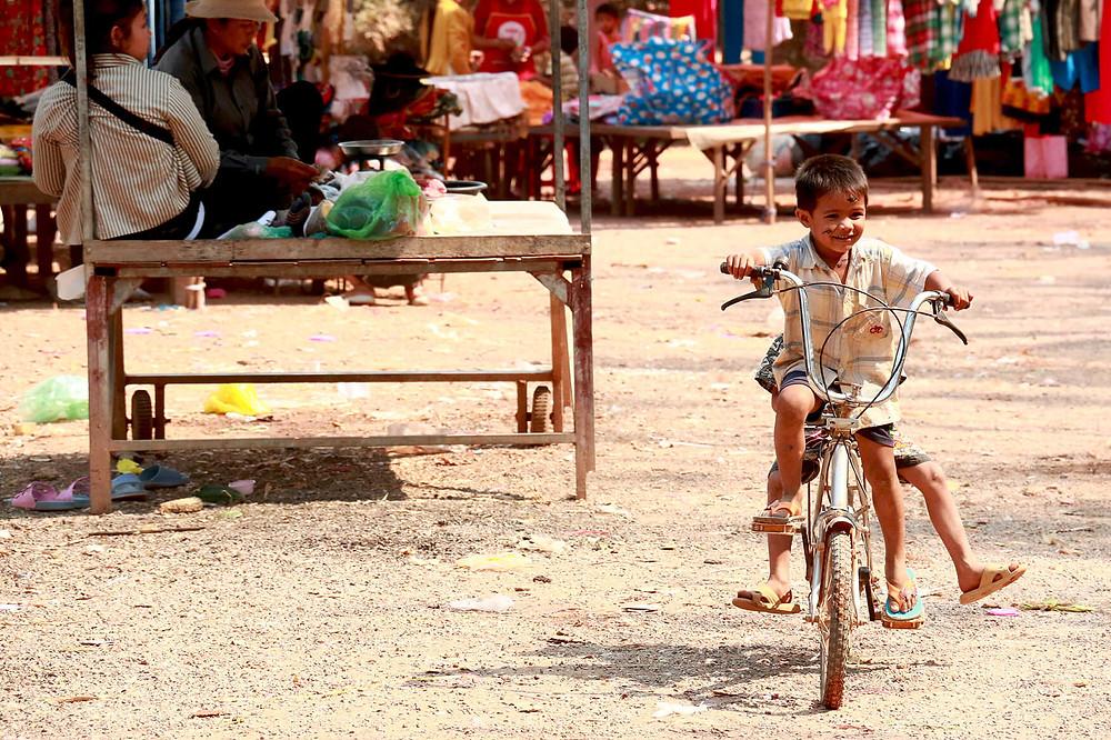 Cambodian kid riding joyfully his bike