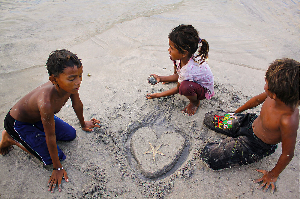 Kids in Indonesia drawing a heart in the sand of a beach