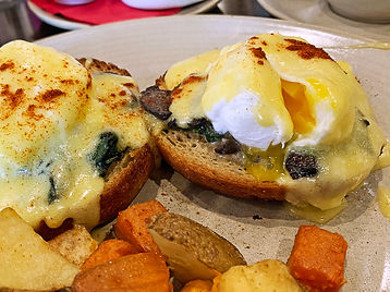 Spinach and mushroom florentine on a buttery brioche muffin with two poached eggs, creamy hollandaise, sweet and local potato hash.