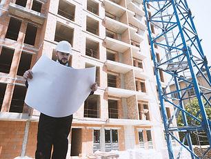 Die Baugenossenschaft Gartenstadt Luginsland eG schafft neuen Wohnraum. Ein Architekt prüft die Baupläne einer Baustelle, hinter ihm ein Rohbau.
