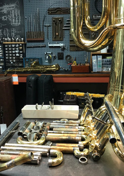Disassembled tuba and a wall ofo dent tools.