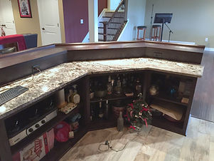 Angled home bar with upper wood top and granite