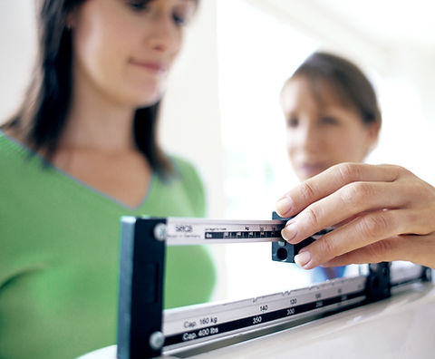 Doctor adjusting balance on weighing scale