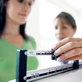 Doctor adjusting balance on weighing sca
