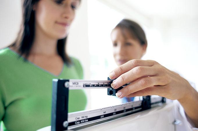 Kirsten Turkington Medical Doctor adjusting balance on weighing scale