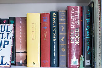 Books on a bookshelf, including Lewis Carroll and Jane Austen.