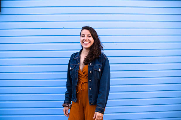 A woman with brown hair smiles into the camera. She stands in front of a blue background.