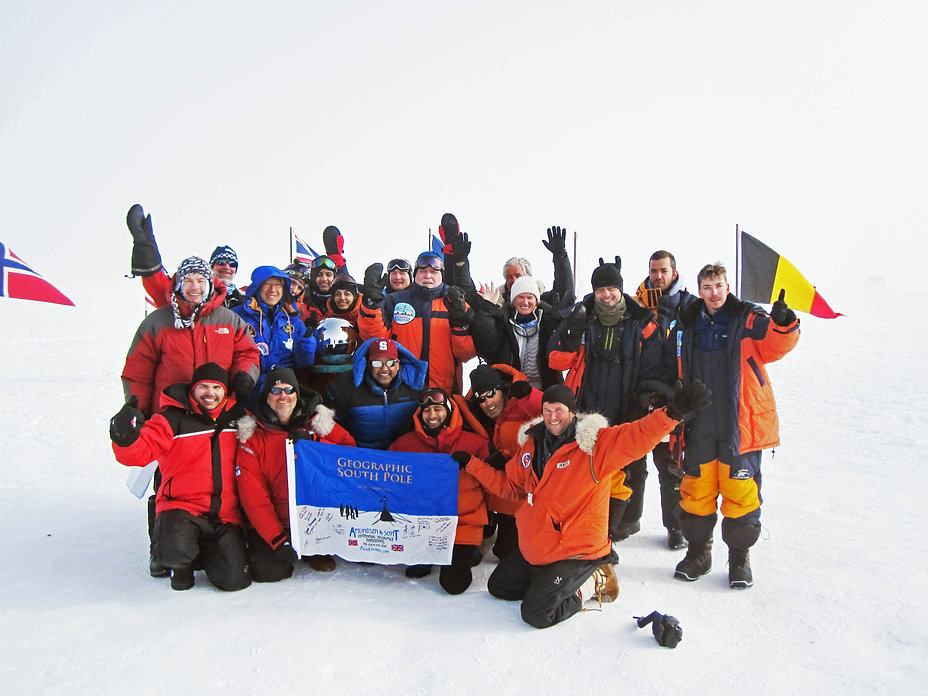 A team celebrates at the South Pole during our South Pole Flight