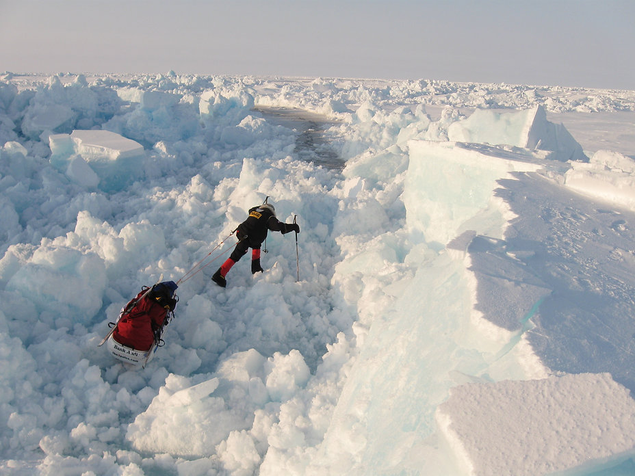 A skier pulls his sled across the broken pack ice of the polar sea on the full-length North Pole Ski Expedition