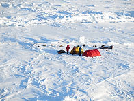 Three explorers and two teams of dogs during the North Pole Dogsled expedition produced by PolarExplorers. The picture is taken from an MI-8 helicopter while flying over the Polar Sea.
