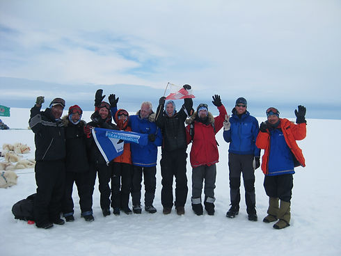 A team of skiers celebrate after skiing across the Greenland Icecap.