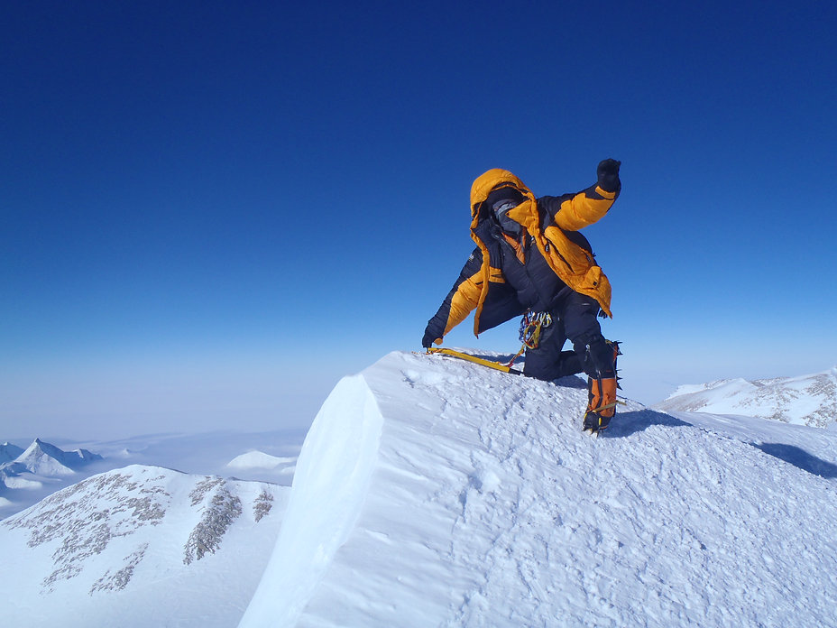 A climber kneels at the summit of Mount Vinson in Antarctic after having climbed mt. Vinson during our South Pole Last Degree / Mt. Vinson combo