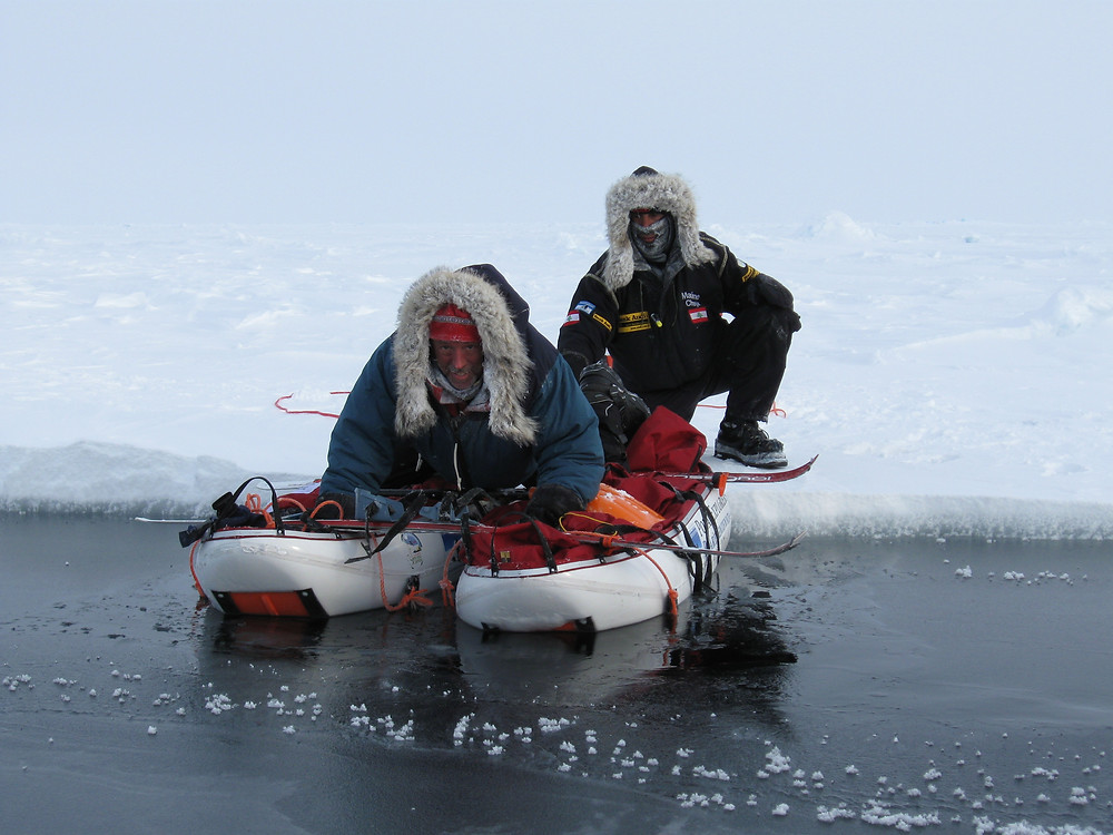 A skier carefully floats on two sleds to cross a lead en route to the North Pole