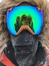 Three skiers on a North Pole Last Degree trek are visible in the reglection of a 4th skiers goggles. Near the Barneo Basecamp on the Polar Sea.