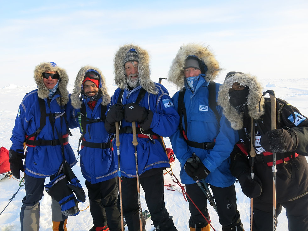 A group of skiers celebrate after skiing the the North Pole on our North Pole Last Degree ski trek.