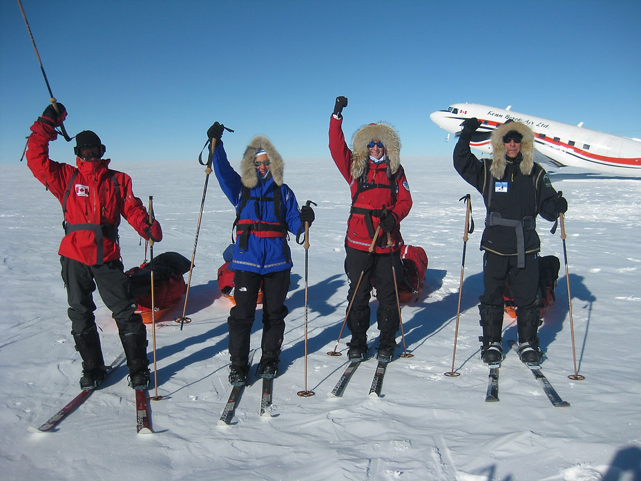 A group of skiers celebrate after skiing the the South Pole on our South Pole Last Degree ski trek.