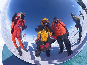 Three people at the Geographic South Pole