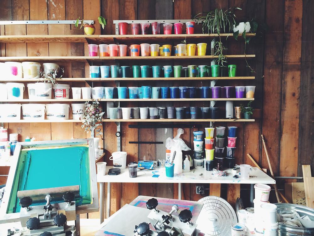The rainbow wall of ink in Adam Porterfield's screenprinting studio