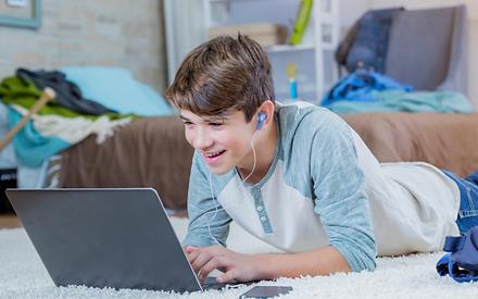 Homeschool teen boy happily using the co