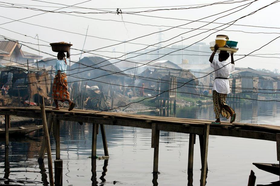 Women carry goods across a makeshift bridge in the Ilaje slum in Lagos. Widening inequality is fuelling tensions across Nigeria.
