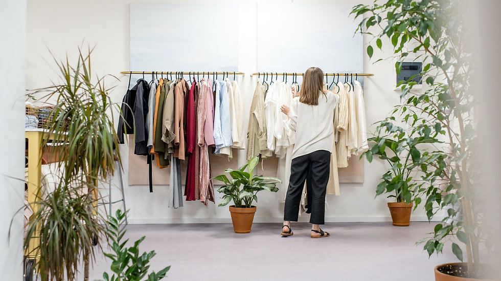 woman standing in front a clothes rack in a clothing store