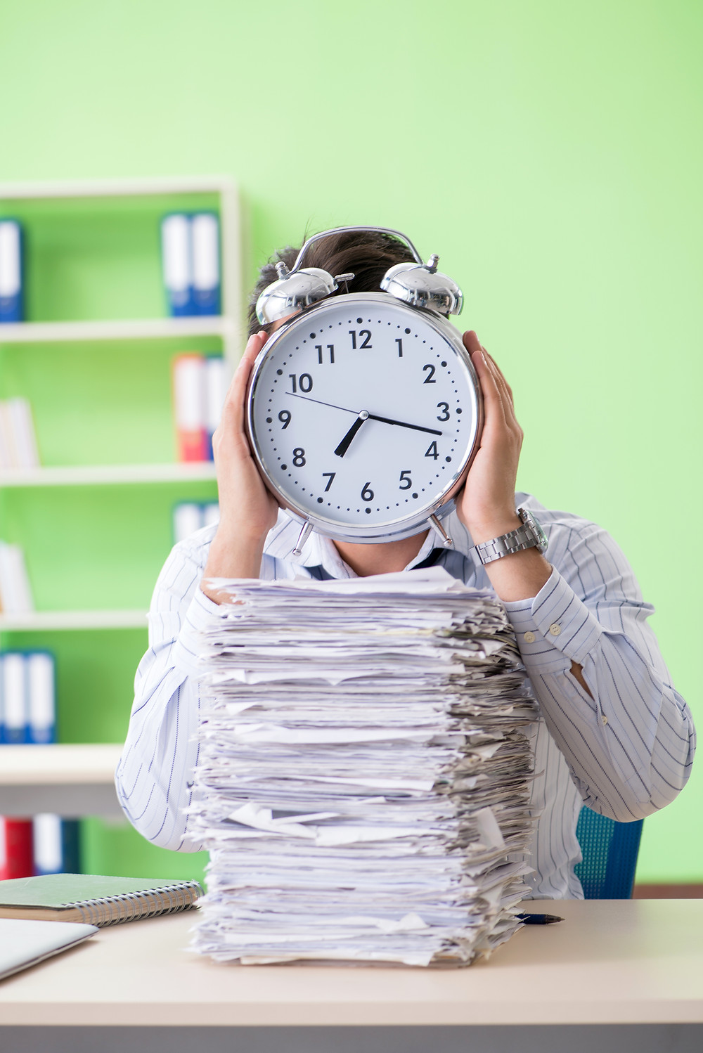 Busy businessman with loads of paperwork and not enough time to do it