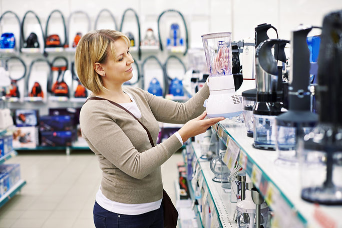 Woman holding an appliance in an appliance retails store
