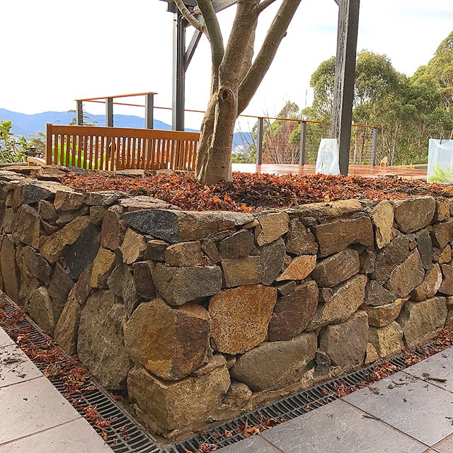 Raised stone wall garden bed on our Clou