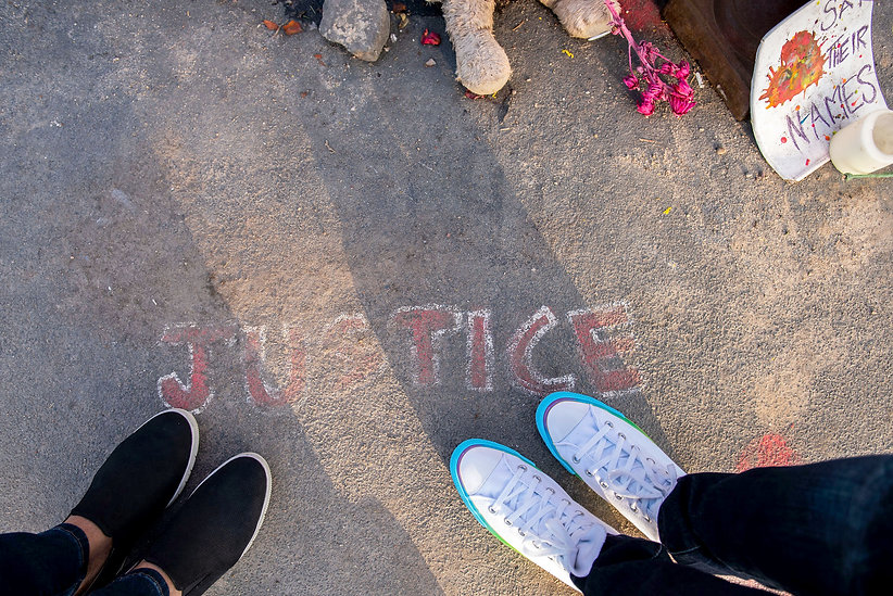 Looking down at sidewalk with 'Justice' written in chalk