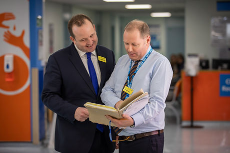 Moorfields Eye Hospital staff standing next to each other looking at documents: David Probert CEO and Gordon Hay, Deputy Director of Education