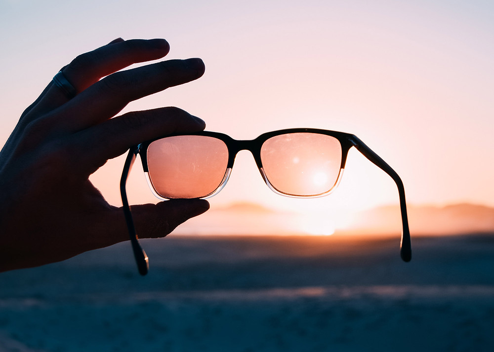 A pair of glasses is held up to the sky in front of a sunset