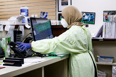 A health worker wearing a facemask, gown and surgical gloves at work using a telephone and computer