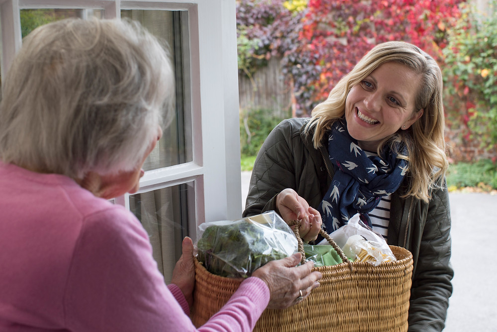 In-home caregiver hands groceries to senior