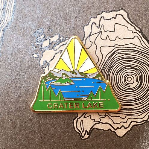 Triangle Crater Lake National Park Hard Enamel Pin featuring a view of Wizard Island from the crater's edge.