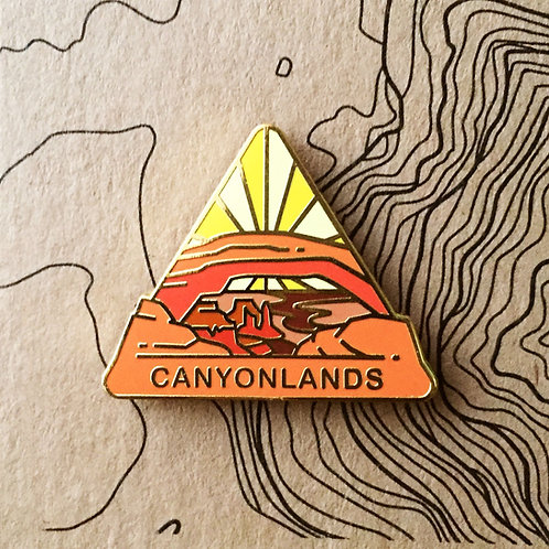 Triangle Canyonlands National Park Hard Enamel Pin featuring the Mesa Arch framing the deep canyon below.