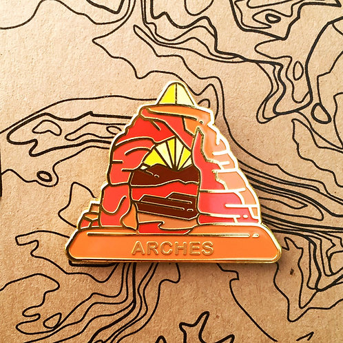 Triangle Arches National Park Hard Enamel Pin featuring a view of the Delicate Arch framing the La Sal Mountains.