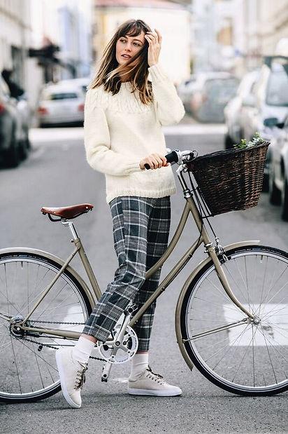 Kvinna med vit sticka tröja korsar gata med cykel