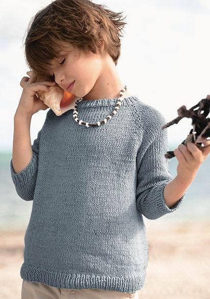 Barn i grå stickad tröja som lyssnar på ett snäckskal