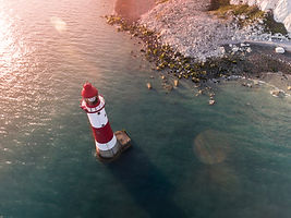 A Drone photo of a lighthouse out at sea