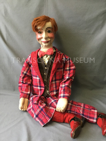 Ventriloquist doll in a red suit.