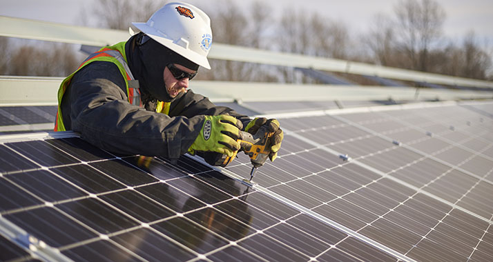 employee-installing-solar-panel-at-gvsu-solar-gardens