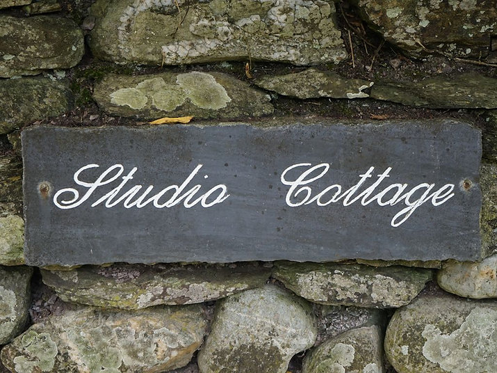 Studio Cottage sign, on a brick wall