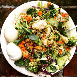 Grain bowl with greens, roasted yams, saudeed and raw veggies, chicken and egg with an avacodo dressing.