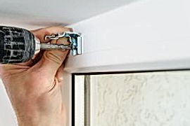installing_wooden_blinds_a_man_attaches_