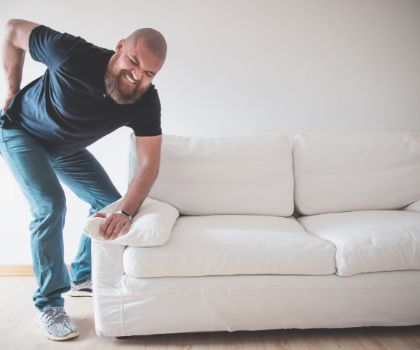 Man picking up a couch with back pain.
